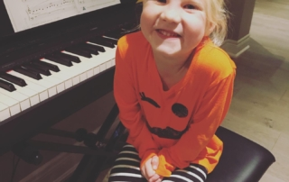 Very happy young piano student sitting in front of piano