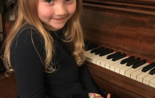 Child at piano smiling for camera during paino lesson