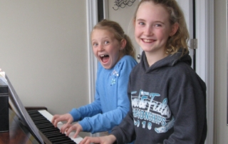 Two students playing on piano with big smiles