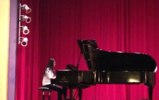 Piano student playing piano on stage at recital