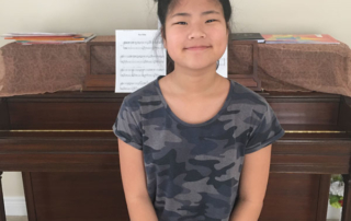 Smiling student sitting in front of piano