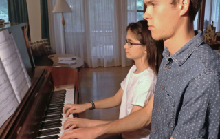 Piano teacher and student playing piano during lesson