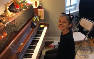 Smiling piano student sitting at piano in halloween costume